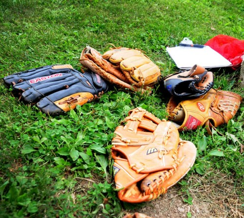 A small pile of baseball gloves on the ground.