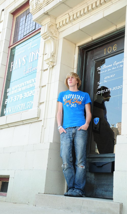 Young man looking away from camera standing in front of a building